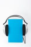 在白色背景的Audiobook 耳机投入了在蓝色精装书书,空的盖子,广告文本的拷贝空间 距离 免版税库存照片