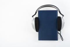 在白色背景的Audiobook 耳机投入了在蓝色精装书书,空的盖子,广告文本的拷贝空间 距离 库存照片