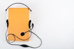 在白色背景的Audiobook 耳机投入了在黄色精装书书,空的盖子,广告文本的拷贝空间 距离 免版税库存图片