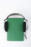 在白色背景的Audiobook 耳机投入了在绿色精装书书,空的盖子,广告文本的拷贝空间 距离 免版税库存照片