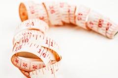 在白色背景的Curled测量的磁带,被射击的特写镜头 免版税图库摄影