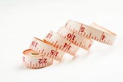 在白色背景的Curled测量的磁带,被射击的特写镜头 免版税库存照片