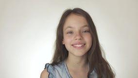 在白色背景股票英尺长度录影的美丽的愉快的十几岁的女孩微笑的特写镜头 股票录像