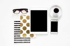在白色背景触摸板片剂小配件手机有金时髦的书的,顶视图的办公桌 库存图片