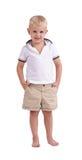 在白色背景隔绝的一个微笑的男孩身分 一个逗人喜爱的孩子在一个夏天穿衣 童年概念 免版税库存照片