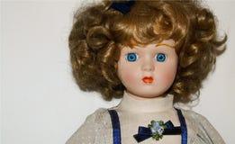 在白色背景隔绝的一个白肤金发的瓷玩偶的特写镜头,葡萄酒戏弄 免版税库存图片