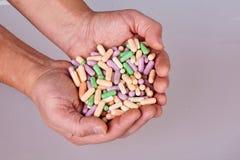 在白色背景隔绝的人的手藏品五颜六色的药片 库存照片