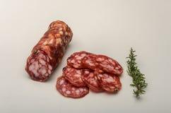 在白色背景隔绝的切的开胃意大利香肠蒜味咸腊肠 库存图片