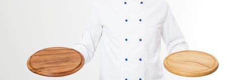 在白色背景隔绝的厨师藏品空的比萨板材,拷贝空间 免版税库存照片