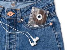 在白色背景隔绝的古板的蓝色牛仔裤和耳机的一个口袋的卡型盒式录音机 库存照片