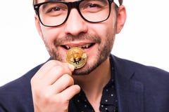 在白色背景隔绝的年轻商人叮咬Bitcoin画象 供以人员叮咬与他的牙的一枚金币 免版税图库摄影