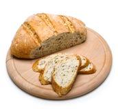 在白色背景隔绝的木切板的新近地被烘烤的面包 免版税库存图片