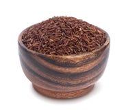 在白色背景隔绝的木碗的红色米 库存图片