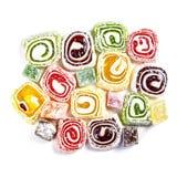 在白色背景隔绝的糖果背景 色的糖果包裹在卷和洒与椰子剥落 图库摄影