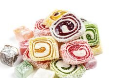 在白色背景隔绝的糖果背景 色的糖果包裹在卷和洒与椰子剥落 免版税库存图片