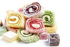 在白色背景隔绝的糖果背景 色的糖果包裹在卷和洒与椰子剥落 库存照片