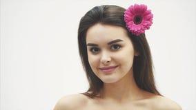 在白色背景隔绝的美丽的年轻美女 在头发的一朵桃红色花,情感,化妆用品 影视素材