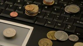 在白色背景隔绝的膝上型计算机的硬币 股票录像