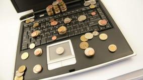 在白色背景隔绝的膝上型计算机的硬币 股票视频