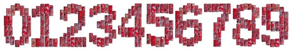 在白色背景隔绝的自然石头的红色数字 库存图片