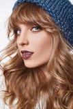 在白色背景隔绝的蓝色帽子的肉欲的白肤金发的妇女 免版税库存照片