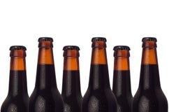 在白色背景隔绝的被密封的黑啤酒瓶装饰边界  酿造工业的设计观念 免版税库存照片