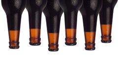 在白色背景隔绝的被密封的黑啤酒瓶装饰边界  免版税图库摄影