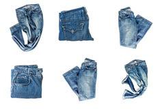 在白色背景隔绝的被折叠的牛仔裤的汇集 免版税库存图片