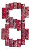 在白色背景隔绝的8自然石头的红色数字 图库摄影