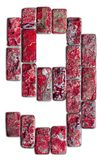在白色背景隔绝的9自然石头的红色数字 免版税库存照片