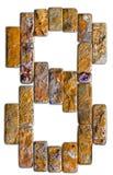 在白色背景隔绝的8自然石头的黄色数字 免版税图库摄影