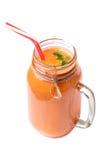 在白色背景隔绝的一个刷新的水多的圆滑的人鸡尾酒的一张顶视图 在泥工的一个健康红萝卜饮料 免版税库存图片