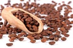 在白色背景隔绝的一个木瓢的咖啡豆 库存图片
