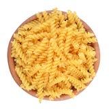 在一个木碗的意大利面团fusilli在白色背景 免版税图库摄影