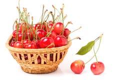 在白色背景隔绝的一个柳条筐的桃红色樱桃 库存图片
