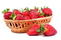 在白色背景隔绝的一个柳条筐的草莓 图库摄影