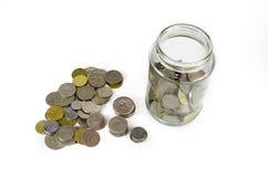 在白色背景隔绝的一个玻璃瓶子内外的硬币 库存照片