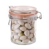 在白色背景隔绝的一个玻璃瓶的开心果 免版税库存图片