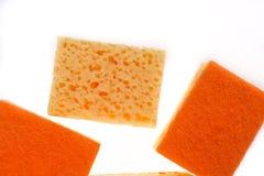 在白色背景隔绝的一块黄色和橙色厨房海绵 库存图片