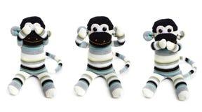 在白色背景隔绝的三只玩具猴子 免版税库存照片