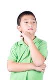 在白色背景隔绝的亚洲男孩认为 图库摄影