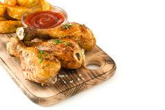 在白色背景隔绝的切板的烤鸡鼓槌 免版税库存图片