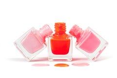 在白色背景隔绝的堆桃红色指甲油 库存照片