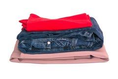 在白色背景隔绝的堆衣裳 牛仔裤,红色和米黄女衬衫 库存照片