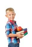 在白色背景隔绝的愉快的男小学生和苹果画象有书的 教育 免版税图库摄影
