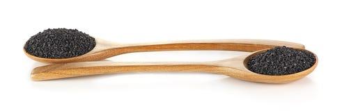 在白色背景隔绝的木匙子的黑芝麻籽 免版税库存照片