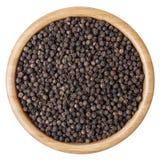 在白色背景隔绝的木碗的黑胡椒玉米 免版税库存照片