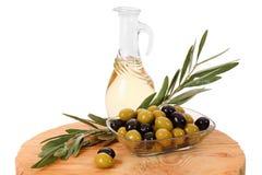 在白色背景隔绝的橄榄油,绿色和黑橄榄 库存图片