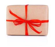 在白色背景隔绝的牛皮纸被栓的红色辫子的礼物 库存照片