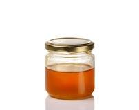 在白色背景隔绝的瓶子清淡的金黄蜂蜜 免版税库存照片